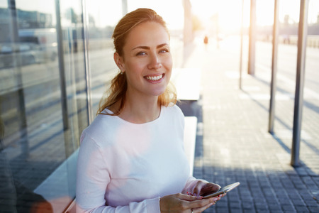 Pretty European woman with beautiful smile holding smart phone while sitting on a bus stop in urban setting, cheerful attractive female using cell telephone while waiting outdoors her friends
