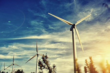 energy sources: Wind turbines against beautiful cloudy sky, electric generators in countryside with sun says on background, renewable energy sources, windmills outside the city