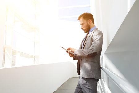 Confident man owner of big successful company using portable touch pad while standing in modern interior near copy space,serious male professional engineer introduces settlements in his digital tablet