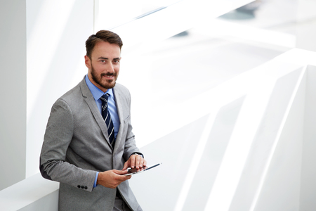 economist: Smiling man skilled economist holding touch pad while standing in modern office interior near copy space,male entrepreneur using digital tablet while waiting beginning interview with new professionals Stock Photo