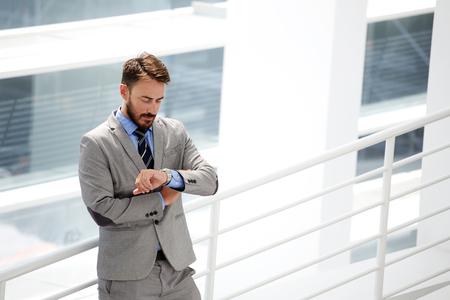 llegar tarde: CEO experto masculino joven en ropa formal, comprobación de tiempo de espera que son socios de negocios a llegar tarde a una reunión, guapo empresario busca en sus relojes de lujo mientras está de pie en la oficina inter