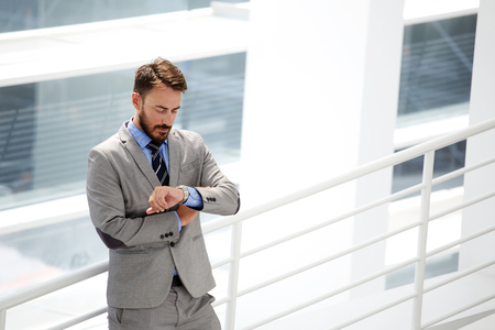 checking time: Young male skilled CEO in formal wear checking time while waiting business partners who are be late for a meeting, handsome businessman looking on his luxury watches while standing in office interior