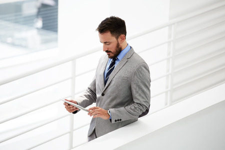 searching information: Young male lawyer searching information on touch pad during work break after business meeting with client, successful man employer checking e-mail via digital tablet while standing in office interior Stock Photo