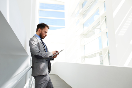 financial official: Young man experienced economist reading financial news in network via touch pad while standing in modern interior, male office worker using his portable digital tablet while waiting start conference Stock Photo