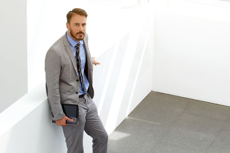 financier: Man successful financier holding touch pad in hand and looking at the camera while waiting beginning of conference, male confident office worker in suit standing with digital tablet in modern interior Stock Photo