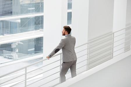 hombre con barba: Arquitecto del hombre que mira profesional objeto de construcción que mediante el uso de recursos logísticos crear un espacio de organización del proyecto, gerente calificado de sexo masculino que mira en la ventana de oficina grande durante su descanso en el trabajo