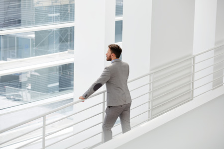 smart man: Man professional architect looks at building object which he by using logistical resources create a project organization space, male skilled manager watching at big office window during his work break Stock Photo