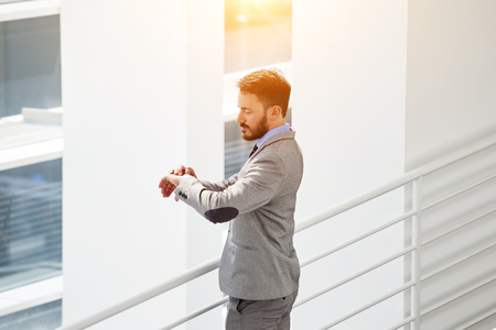 checking time: Young male successful employer dressed in luxury suit checking time to begin interview with the specialists, confident businessman looking at watches on hand while standing inside his thriving company