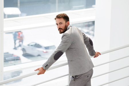 economist: Half length portrait of wealthy male economist dressed in classic suit looking back while standing near window in office hallway, smart man banker waiting for his partners before starts conference