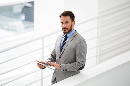 financier: Half length portrait of rich businessman holding portable digital tablet during work break in hallway, confident young male financier count the costs via touch pad while standing in office interior Stock Photo