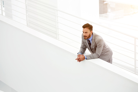 Thoughtful young male CEO thinking about growth his career while standing in modern office hallway, serious man manager looking away during rest in work break after big presentation of new project Imagens - 59389992