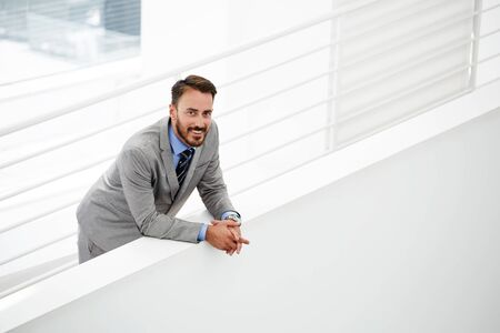 Half length portrait of intelligent male lawyer feeling happy after winning court case while standing in modern hallway, smiling young businessman dressed in classic suit resting after conference