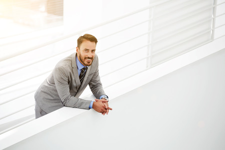 formal wear: Half length portrait of happy young businessman in formal wear standing near copy space in modern interior, smiling bearded male manager resting in office hallway after successful meeting with clients Stock Photo