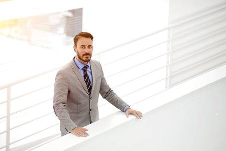 half dressed: Half length portrait of confident male business owner standing in office building inside during work day, elegant man employee dressed in luxury suit posing in modern hallway of his big company