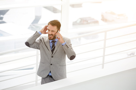 baffled: Baffled male engineer having bad conversation via mobile phone before meeting with international partners, bemused man architect talking on cell telephone while standing in modern office interior