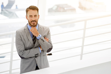 half dressed: Half length portrait of smiling young skilled businessman standing near copy space in modern office interior, portrait of happy male entrepreneur owner of prosperous company dressed in luxury suit