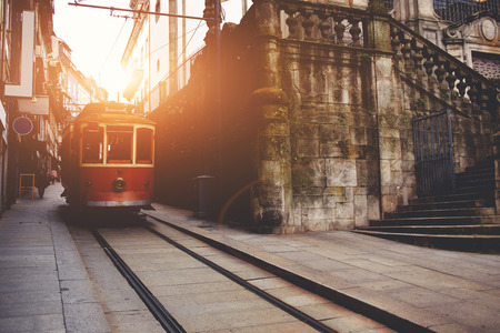 urban scene: Traditional vintage tram makes its way across central streets in old city in sunny morning, public transport on metallic rails standing near architectural monument, electrical streetcar in urban scene