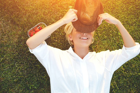 day break: Cheerful young woman closes own eyes from the sunlight using stylish hat while enjoying summer vacation, hipster girl with beautiful smile hiding face under headgear while lying on the grass in park