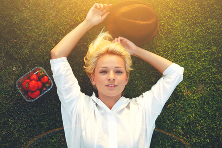 prettiness: Top view of young charming female enjoying rest after strolling while lying down on the green grass in sunny summer day, pretty blonde hair woman with trendy hat and box of strawberries posing in park