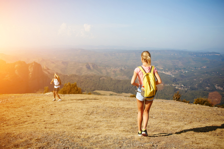 rucksacks: Back view of young blonde woman standing on a mountain hill and waiting her friend which standing below, two active male and female person hiking together with rucksacks in sunny summer day outdoors