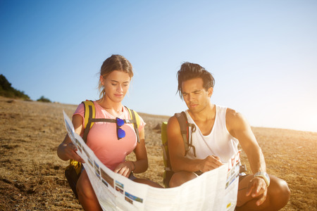 wanderers: Man and woman wanderers exploring map while sitting on a mountain hill in sunny summer day during their weekend,two travelers searching road on atlas while taking break after hiking in the countryside Stock Photo