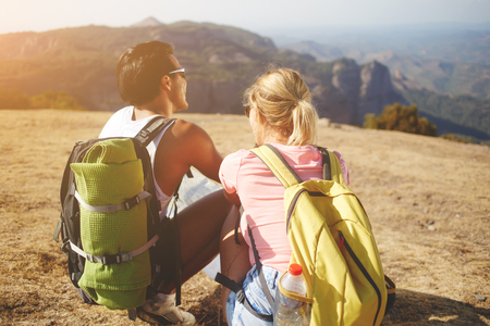 wanderers: Back view of a young man and woman enjoying amazing nature landscape during their summer trip overseas, two wanderers sitting on a high mountain while resting after hiking in beautiful sunny day Stock Photo