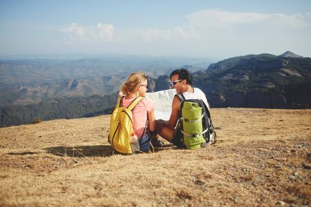 wanderers: Cheerful man and woman wanderers holding map while sitting on a mountain hill against beautiful nature landscape, smiling two hikers enjoying rest after hiking during their long awaited summer weekend Stock Photo