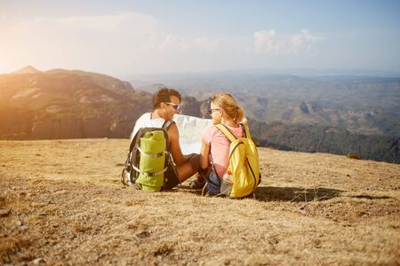 wanderers: Young man and woman wanderers with good mood holding map while sitting on a high hill against amazing view, cheerful happy tourists resting after walking in mountainous areas during summer adventure