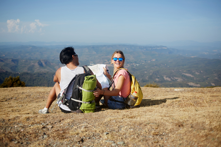 wanderers: Young man and woman with a rucksack on back sitting with map on high mountain hill against beautiful view, two happy wanderers relaxing after hike in summer sunny day during their long awaited journey