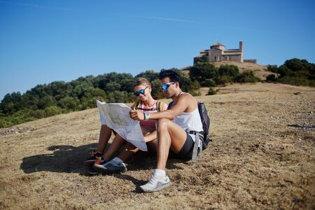 wanderers: Young man and woman travelers exploring map to continue hiking tour in the countryside in sunny day, two wanderers studying atlas while sitting on a mountain during their summer adventure overseas
