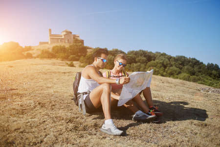 wanderers: Two young travelers exploring map while sitting on a mountain hill in sunny summer day during long awaited vacation, man and woman wanderers studying atlas before start their walking in the highlands Stock Photo