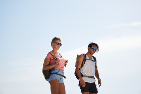 wanderers: Smiling man and woman travelers with rucksack on back standing against blue sky background with copy space, happy cheerful wanderers taking break between walking in the countryside in summer day