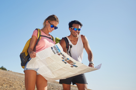 wanderers: Smiling happy man and woman travelers studying map to continue walking in the mountains in sunny day, young cheerful wanderers exploring atlas before the start hiking during summer adventure Stock Photo