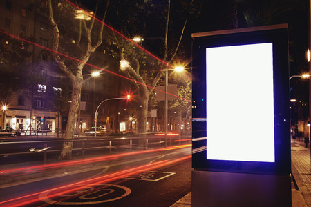 Illuminated blank billboard with copy space for text message or promotional content, public information board in night city with cars light on background, advertising mock up banner in urban setting