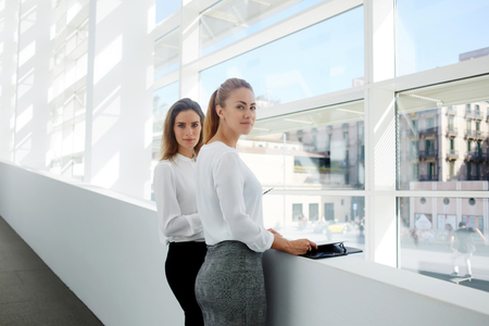 confidentially: Two female partners in good mood preparing for interview with documents while they standing in modern office interior, elegant women managers dressed in formal wear posing near big window in hallway Stock Photo