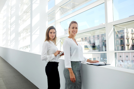 formal wear: Team of successful women financiers with touch pad and documents posing while standing in modern office interior, two smiling female lawyers in formal wear resting after presentation on digital tablet