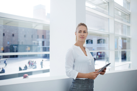 Young woman successful financier in formal wear taking break between work on portable digital tablet, female skilled entrepreneur holding touch pad and thinking about ideas before meeting with client