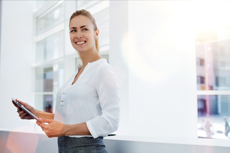 Happy woman manager holding touch pad and thinking about something good while standing in modern office interior,young smart female secretary smiling for someone during work on portable digital tablet Standard-Bild