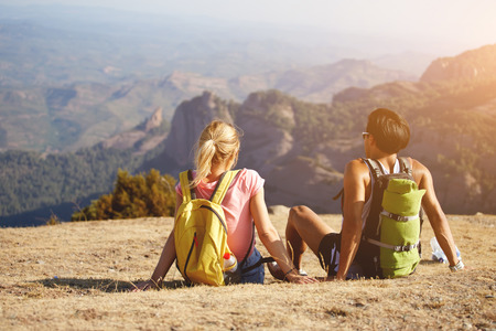 rucksacks: Back view of a two wanderers with rucksacks sitting on a high mountain during their journey overseas, young man and woman relaxing in the fresh air after hiking  in highlands during summer adventure