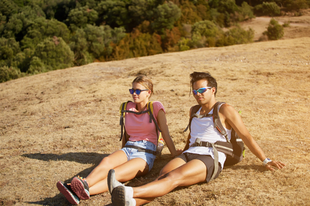 wanderers: Tired man and woman travelers enjoying beautiful landscape while sitting on a hill in sunny summer day, young two wanderers relaxing outdoors after hiking in mountain during their vacation overseas
