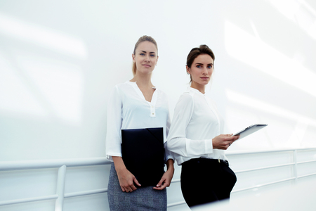 confidentially: Half length portrait of a businesswomen posing with touch pad and paper documents in office interior, young two female lawyers with confident look standing with digital tablet in corridor company