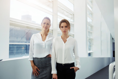 half dressed: Half length portrait of a confident businesswomen dressed in formal wear posing in modern office interior, team of professional female employees resting after big conference while standing in hallway Stock Photo