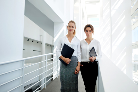 confidentially: Serious female colleagues dressed in formal wear with digital tablet and documents returning after meeting with employers, woman lawyer with touch pad standing near her co-worker in office interior