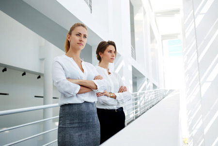 competitividad: Half length portrait of a two successful financiers with serious look posing in modern office interior, team of female leaders ponders over the future of company during work break in office hallway