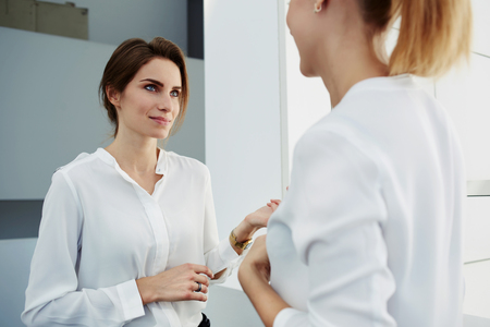 Two female managing directors discussing pros and cons of new project while standing in office interior, young women financiers dressed in formal wear having met in office hallway during work break Stock Photo