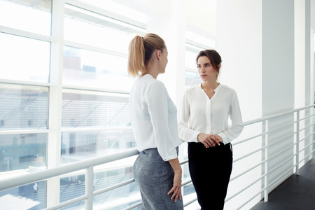 formal wear: Elegant women entrepreneurs speaking about something personal while standing near office window, two European female managers dressed in formal wear have met in company corridor during work break