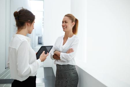 ejecutiva en oficina: Secretaria sonriente mujer hablando con abucheos mientras está de pie en el interior de la oficina moderna durante la rotura de trabajo, mujer con panel táctil mientras habla con su socio de negocios durante reunido en compañía pasillo Foto de archivo