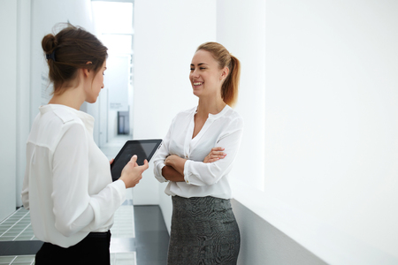 office break: Smiling female secretary talking with boos while standing in modern office interior during work break, woman holding touch pad while speak with her business partner during met in hallway company Stock Photo