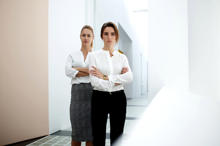 formal wear: Team of two female skilled employees standing side by side in modern office interior, women prosperous partners in formal wear standing with crossed arms, concept of reliability and performance