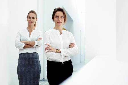 competitividad: Par de un joven dos trabajadores profesionales femeninos vestidos de corporativos de pie con los brazos cruzados en interior de la oficina, mujeres de negocios prósperos con mirada de confianza que presentan en compañía de pasillo